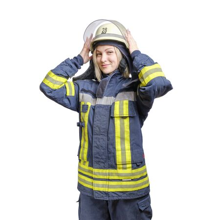 Photo pour young smiling girl firefighter puts a helmet on his head. isolated on white background - image libre de droit