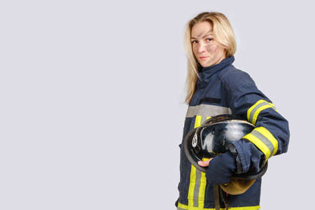 Photo pour Young brave woman with dirty face in uniform of firefighter holds hardhat in hand and looking at camera isolated on gray background. - image libre de droit