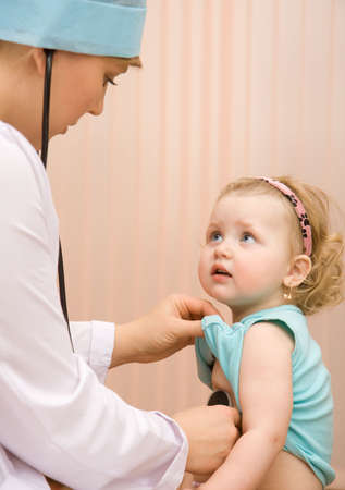 Doctor pediatrician examines little child using stethoscope
