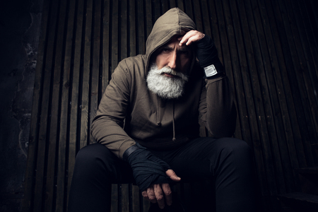 Foto de Serious bearded man ready to fight. Sport and fit man in hood thinking about future fight. Workout and box sport. Extreme sport for old man. Close up portrait of man hands over his sports bandages - Imagen libre de derechos