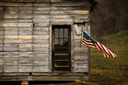 American Flag hanging from an old barn with negative space to display text.