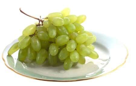 Big branch of green grape on plate isolated