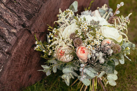 Foto de rustic wedding bouquet with roses and succulents on green grass and wooden texture - Imagen libre de derechos