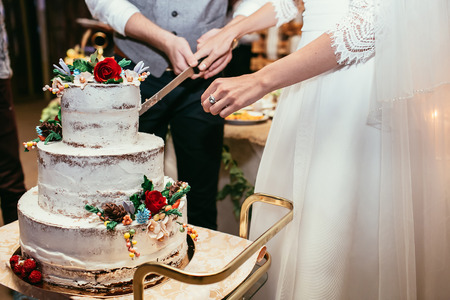 bride and groom cut rustic wedding cake on wedding banquet with red rose and other flowers