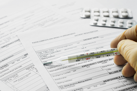 Thermometer in man hand on patient registration form
