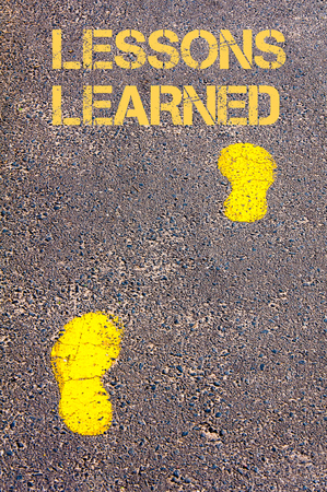 Yellow footsteps on sidewalk towards Lessons Learned message.Conceptual image