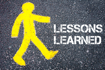 Yellow pedestrian figure on the road walking towards LESSONS LEARNED. Conceptual image with Text message over asphalt background.