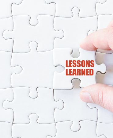 Missing jigsaw puzzle piece with words LESSONS LEARNED. Business concept image for completing the puzzle.