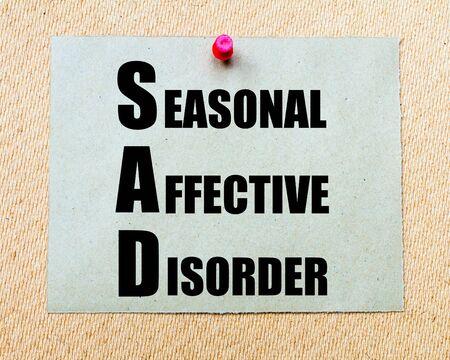 SAD as Seasonal Affective Disorder written on paper note written on paper note pinned with red thumbtack on wooden board. Health conceptual Image