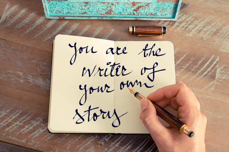 Retro effect and toned image of a woman hand writing a note with a fountain pen on a notebook. Motivational concept with handwritten text YOU ARE THE WRITER OF YOUR OWN STORY