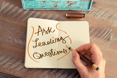 Retro effect and toned image of a woman hand writing a note with a fountain pen on a notebook. Handwritten text ASK LEADING QUESTIONS, business success concept