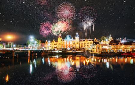 Foto de Beautiful calm night view of Amsterdam city. Colorful fireworks on the black sky background. Photo greeting card. Bokeh light effect, soft filter. - Imagen libre de derechos