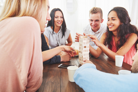 Photo pour Group of creative friends sitting at wooden table. People having fun while playing board game - image libre de droit