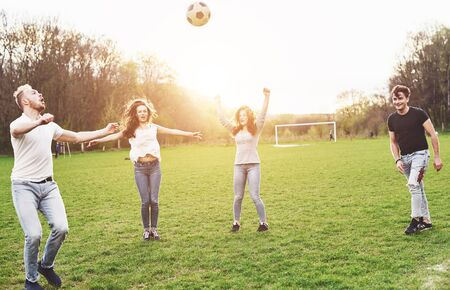 Photo pour A group of friends in casual outfit play soccer in the open air. People have fun and have fun. Active rest and scenic sunset - image libre de droit