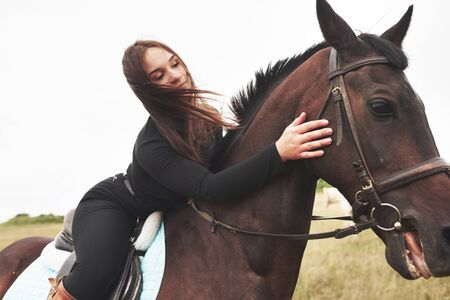 Photo for Young cute girl hugging her horse while sitting astride. She likes animals. - Royalty Free Image