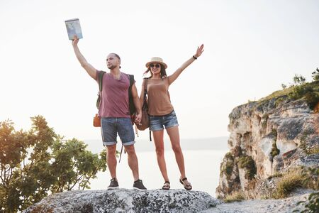 Photo pour Two tourist male and woman with backpacks stand to the top of the crag and enjoying sunrise. Traveling mountains and coast, freedom and active lifestyle concept. - image libre de droit