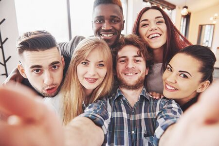 Photo pour Friends having fun at restaurant. Three boys and three girls making selfie and laughing. On foreground boy holding smart phone. All wear casual clothes. - image libre de droit