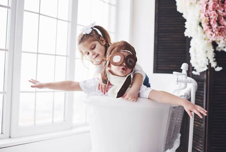 Photo pour Portrait of a girl and a boy in pilot hat playing in bathroom at pilots or sailors. The concept of travel, childhood and the realization of dreams. - image libre de droit
