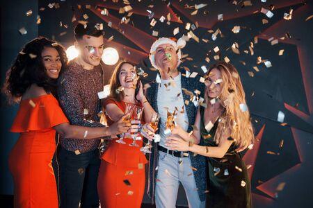 Foto de A group of friends posing and having fun with snowmen and champagne. New Year Celebration - Imagen libre de derechos