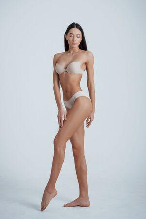 Foto de Full height photo of young brunette girl in white underwear standing at white background. - Imagen libre de derechos