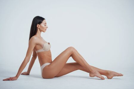 Photo pour Like on the beach. Girl with perfect slim toned young body sitting in the studio with white background behind. - image libre de droit