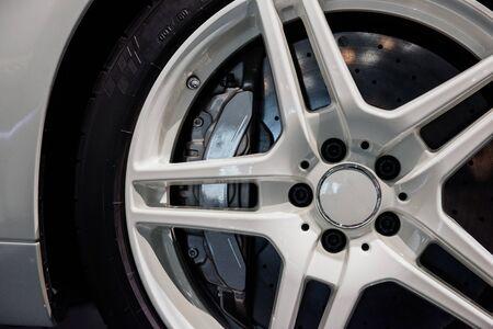 Photo pour Close up shot of white light alloy wheels with brake disc pad, low-profile tires of a modern sport car. - image libre de droit