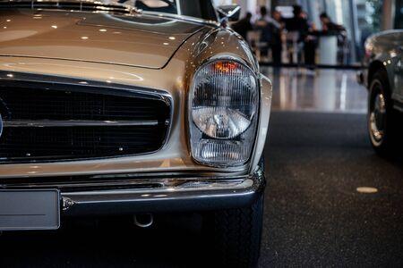 Photo pour Close-up of the left headlight of retro beige cabriolet car with chrome side mirror, bumper and radiator trim. - image libre de droit