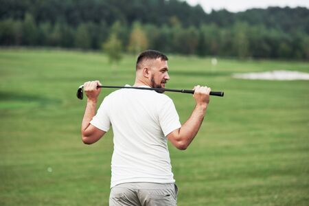 Photo pour Holding stick behind. Portrait of walking golf player in the lawn and equipment in hand. Woods at background. - image libre de droit