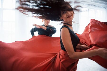 Photo pour Photo of motion. Young pretty woman in red and black clothes dancing with bald guy in the white room. - image libre de droit