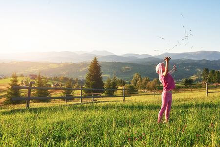 Photo pour Cute happy little baby girl play outdoors in the early morning in the lawn and admiring mountains view. Copy space for your text. - image libre de droit