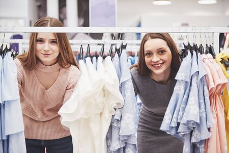 Foto per Young beautiful women at the weekly cloth market - Best friends sharing free time having fun and shopping in the old town in a sunny day - Girlfriends enjoying everyday life moments. - Immagine Royalty Free
