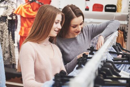 Foto per Young beautiful women at the weekly cloth market - Best friends sharing free time having fun and shopping. - Immagine Royalty Free
