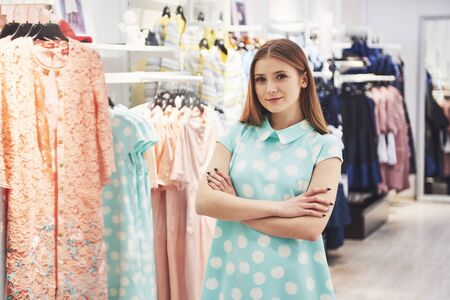 Photo pour Woman shopping clothes. Shopper looking at clothing indoors in store. Beautiful happy smiling asian caucasian female model. - image libre de droit