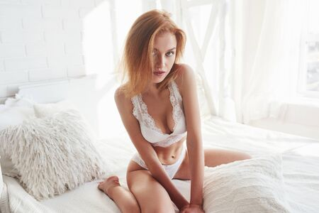 Photo pour Nice ginger haired young woman. Portrait of a sexy redhead girl sitting on the bed and posing in the white room. - image libre de droit
