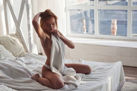 Photo pour Looking down. Hot redhead girl sits on the white bed with no bra. Covering chest with towel. - image libre de droit