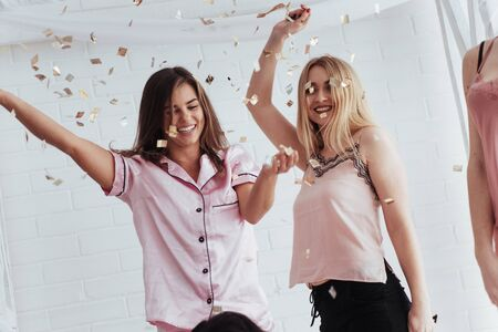 Photo pour Emotional faces. Confetti in the air. Young girls have fun on the white bed in nice room. - image libre de droit
