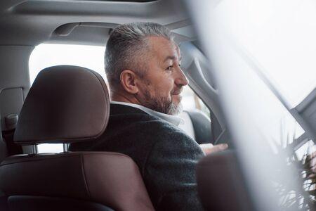 Photo pour Happy owner. Rear view of senior businessman in official clothes driving a modern new car. - image libre de droit