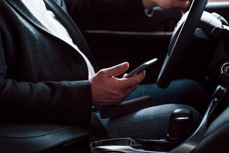 Photo pour Rich clothes, car and mobile device. Working in the car using silver colored smartphone. Senior businessman. - image libre de droit