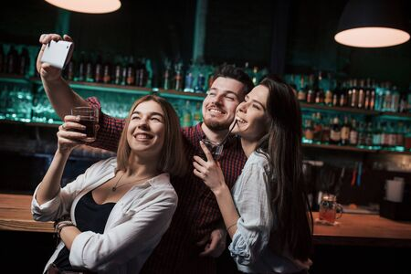 Photo for Many bottles with alcohol behind. Friends taking selfie in beautiful nightclub. With drinks in the hands. - Royalty Free Image