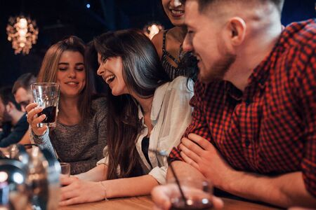 Photo pour Hard laughings. Beautiful youth have party together with alcohol in the nightclub. - image libre de droit
