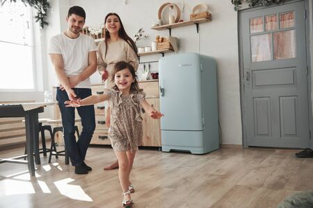 Photo pour Looking at the daughter. Playful female child have fun by running in the kitchen at daytime of front of her mother and father. - image libre de droit