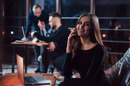 Photo pour Charmful positive woman. Team of young business people works on their project at night time in the office. - image libre de droit