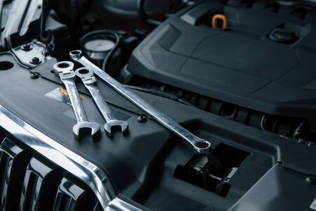 Photo for Black colored interior. Repair tools lying down on the engine of automobile under the hood. - Royalty Free Image