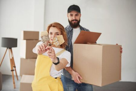 Photo for Crossed brushes in hands. Happy couple together in their new house. Conception of moving. - Royalty Free Image