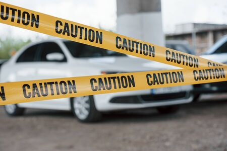 Photo for Restricted area. Yellow caution tape near the car parking lot at daytime. Crime scene. - Royalty Free Image