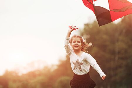 Photo pour Amazing sunlight. Happy girl in casual clothes running with kite in the field. Beautiful nature. - image libre de droit