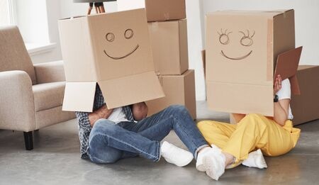Photo for Smiles on boxes. Happy couple together in their new house. Conception of moving. - Royalty Free Image