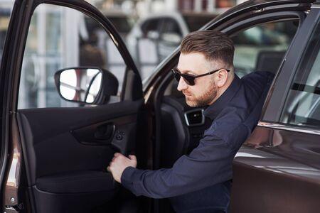 Photo pour How it feels. Man in official clothes trying his new car in automobile salon. - image libre de droit