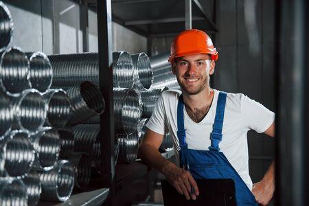 Photo pour Sincere smile. Man in uniform works on the production. Industrial modern technology. - image libre de droit