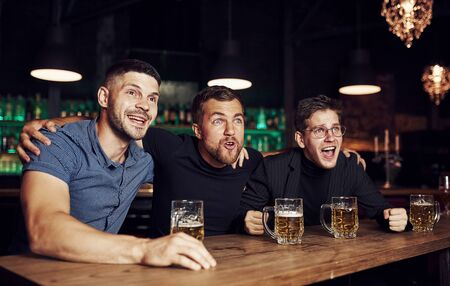 Photo for Three sports fans in a bar watching soccer. With beer in hands. - Royalty Free Image